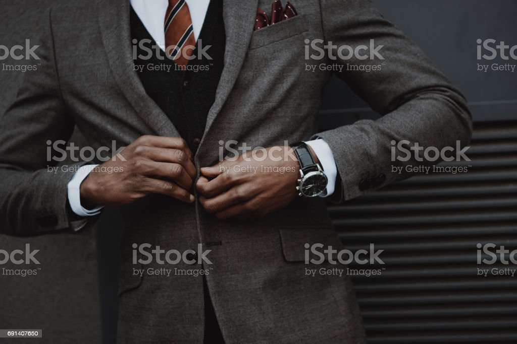 confident stylish businessman wearing suit outdoors at wall stock photo