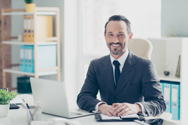 Confident success handsome good-wearing style stylish man in chi Confident success handsome good-wearing style stylish man in chic formalwear sit on comfort armchair behind desktop in bright white office make beaming toothy smile director stock pictures, royalty-free photos & images
