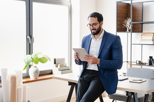 Confident successful arabian businessman tutor freelancer CEO working on digital tablet, watching webinars, e-learning, checking e-mails social media, reading news. Middle Eastern financial advisor