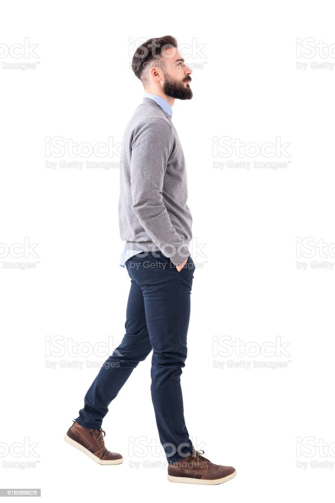 Confident successful smart casual businessman walking with hands in pockets - fotografia de stock