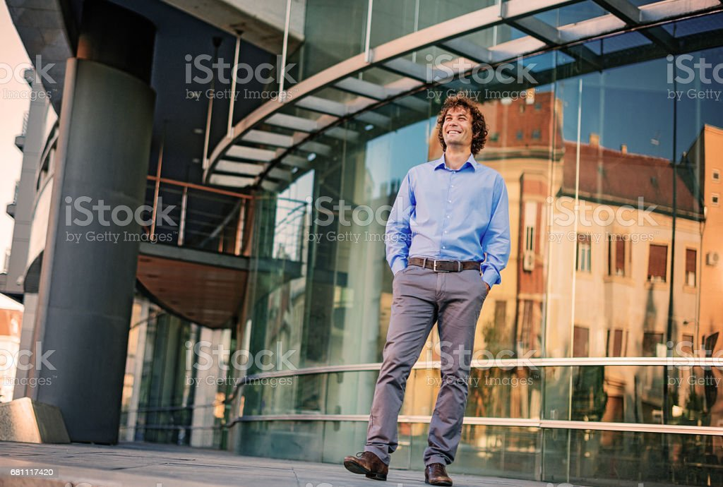 Confident successful young man smiling near office building royalty-free stock photo