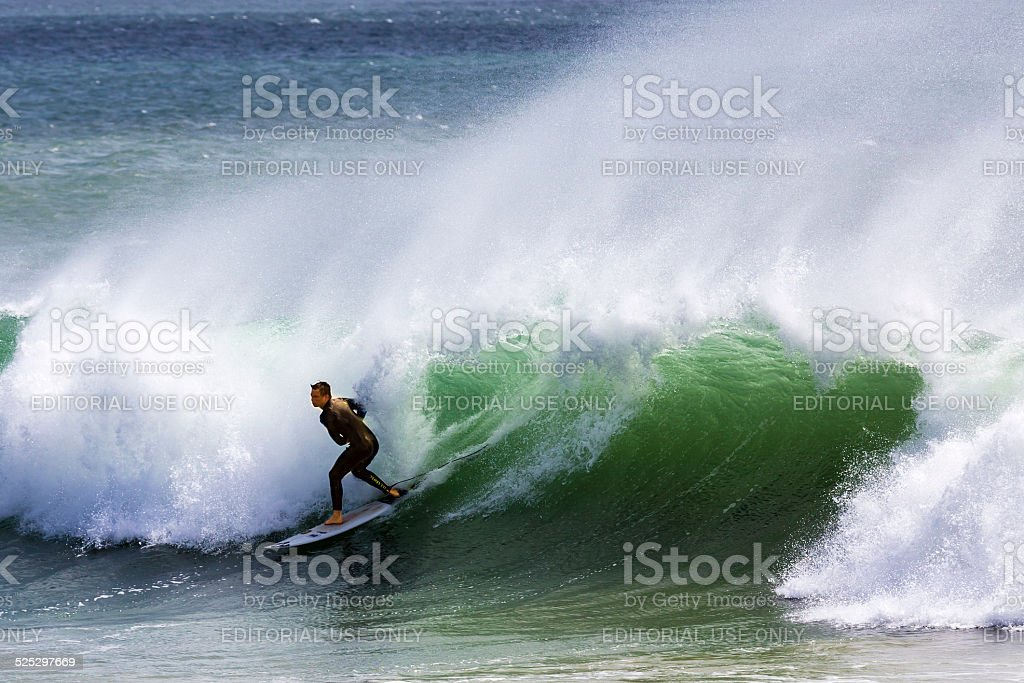 Confident surfer at sea riding the wave stock photo