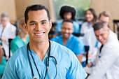 Mid adult Hispanic medical professional smiles while attending a medical seminar. He is wearing blue scrubs and a stethoscope. People are sitting in the background.