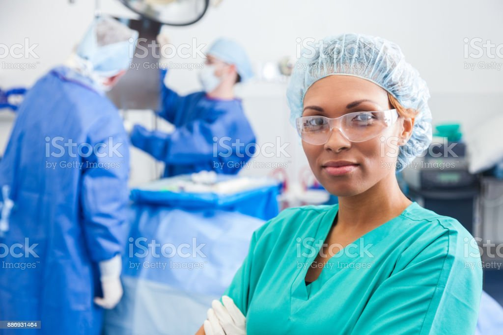 Confident surgical nurse prepares to assist surgeon Confident female surgical nurse prepares for surgery. Surgeons are in the background. Accuracy Stock Photo