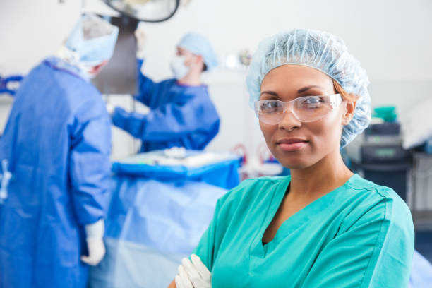 Confident surgical nurse prepares to assist surgeon Confident female surgical nurse prepares for surgery. Surgeons are in the background. anesthetize stock pictures, royalty-free photos & images