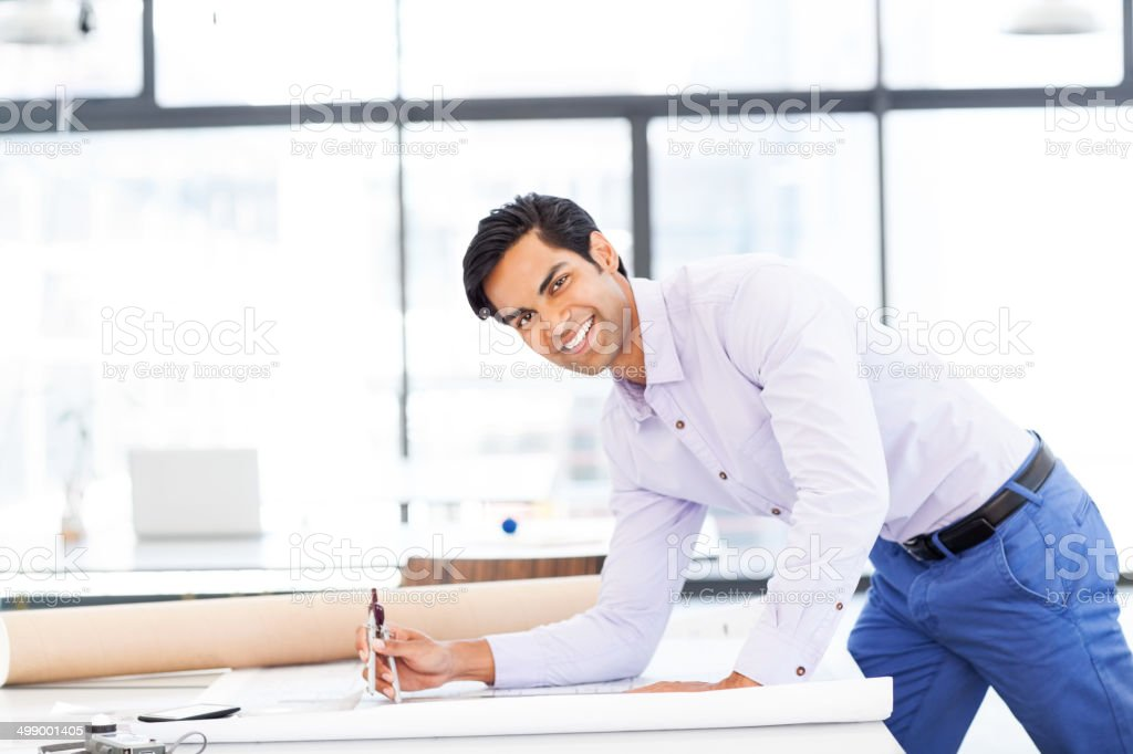 Confident Surveyor Working On Blueprint In Office royalty-free stock photo