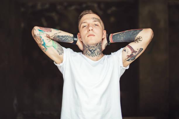 Confident tattooed man posing outside stock photo