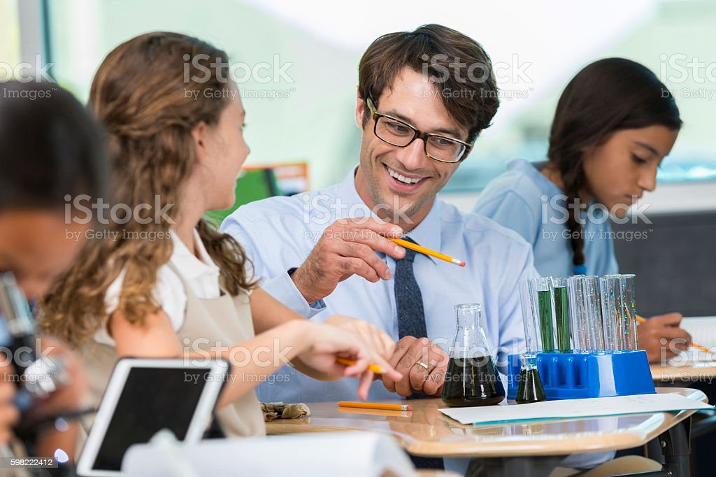 Confident teacher works with students in science class foto royalty-free