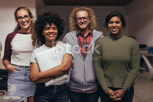 Portrait of young people standing together at startup office looking at camera and smiling. Confident team to IT professionals.