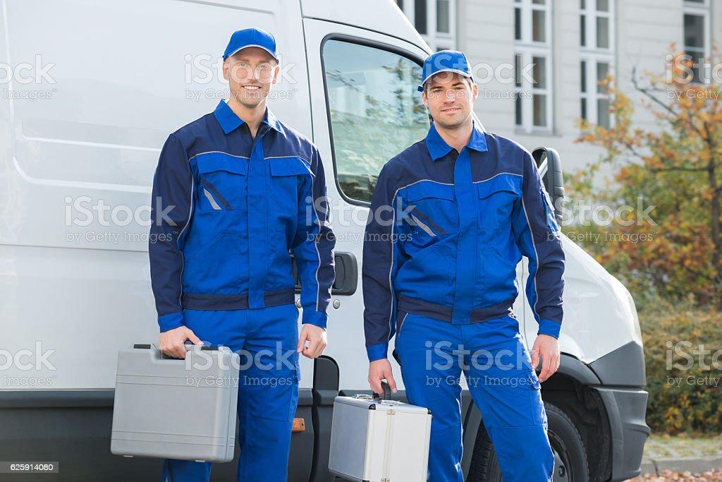 Confident Technicians Standing Against Truck stock photo