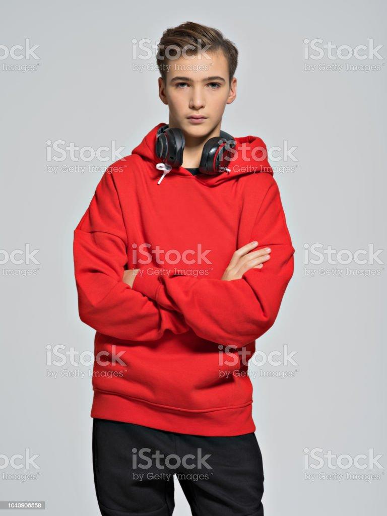 Handsome teenage boy with headphones over neck. Confident teen with...