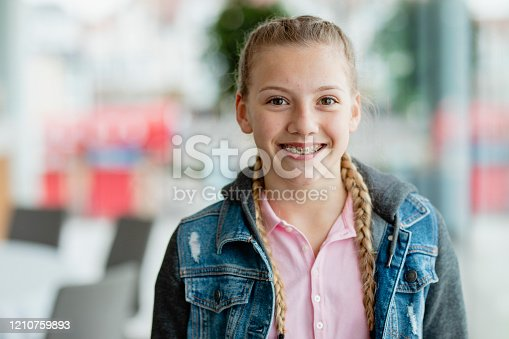 Adolescent blond girl with plaits smiling confidently, youth, aspiration, growing up
