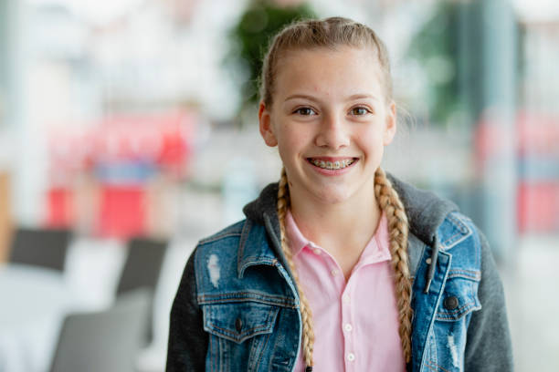 Confident teenage girl with braces, smiling at camera stock photo