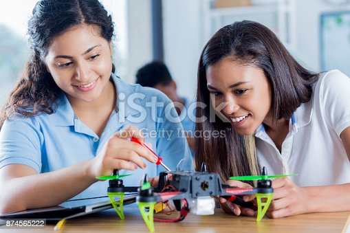 istock Confident teenage girls build drone during science class 874565222
