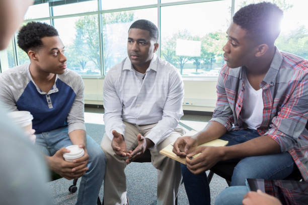 Confident therapist leading group therapy session Mid adult African American male therapist discusses something with young men during a group therapy session. The men are attentively listening to the therapist. group therapy stock pictures, royalty-free photos & images
