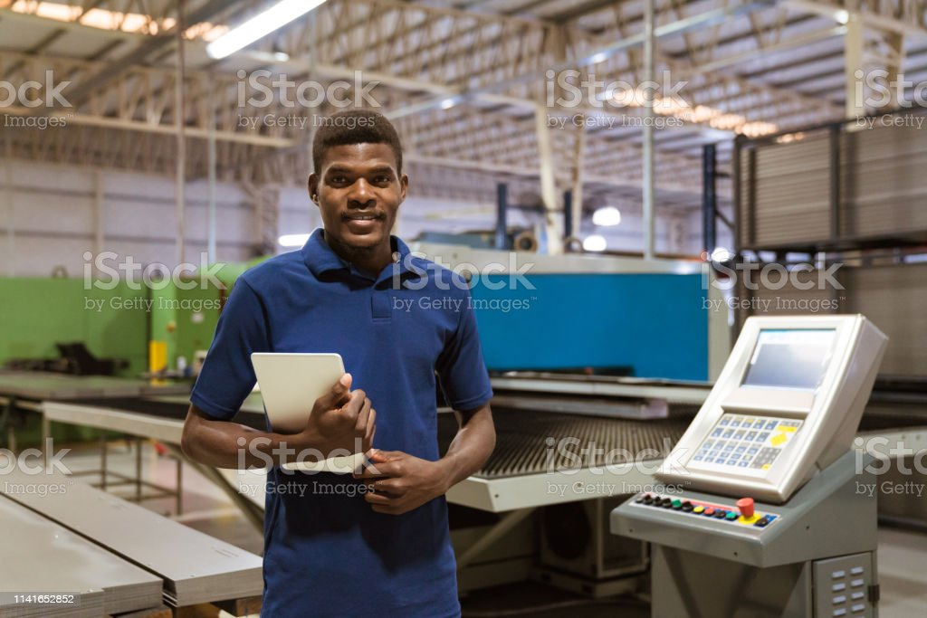 Confident trainee holding digital tablet in industry Portrait of confident trainee holding digital tablet. Male is smiling while standing in industry. He is in uniform at factory. 25-29 Years Stock Photo