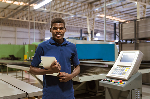 Confident Trainee Holding Digital Tablet In Industry Stock Photo - Download Image Now