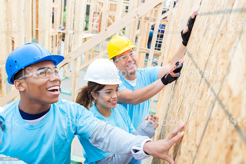Confident volunteers build wall in charity home stock photo