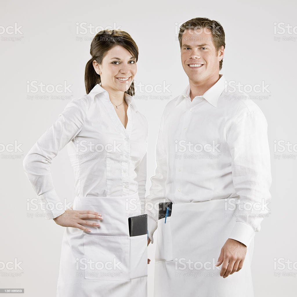 Confident waiter and waitress in aprons with order pads royalty-free stock photo