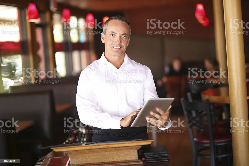 Confident Waiter Holding Tablet Computer In Restaurant royalty-free stock photo