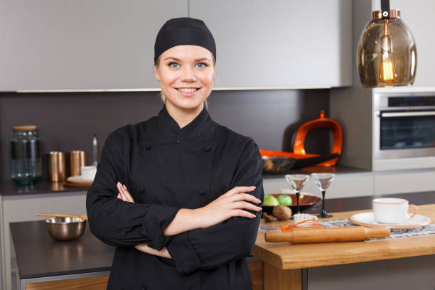 Confident woman chef Portrait of confident young woman personal chef in black uniform standing in stylish interior of home kitchen military private stock pictures, royalty-free photos & images