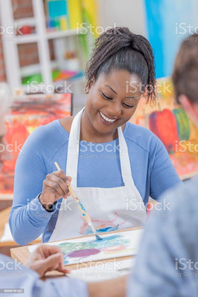 Mulher confiante desfruta de pintura com os amigos - foto de acervo
