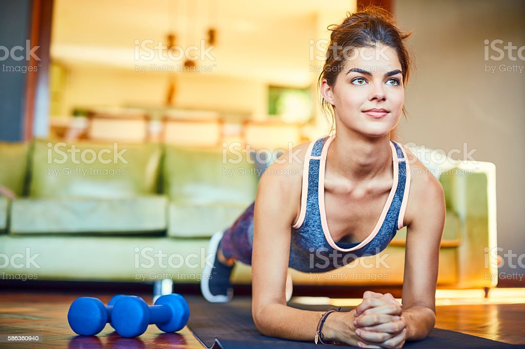 Confident woman exercising in plank position at home stock photo