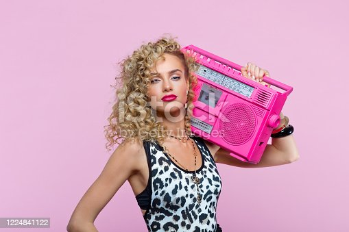 807419930 istock photo Confident woman in 80's style outfit holding boom box 1224841122