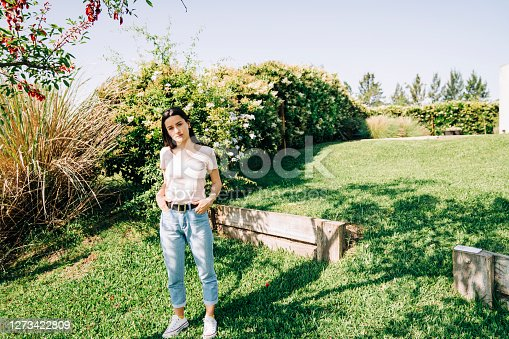 Confident woman in backyard during sunny day. Young female is standing with hands in pockets. She is wearing casuals.