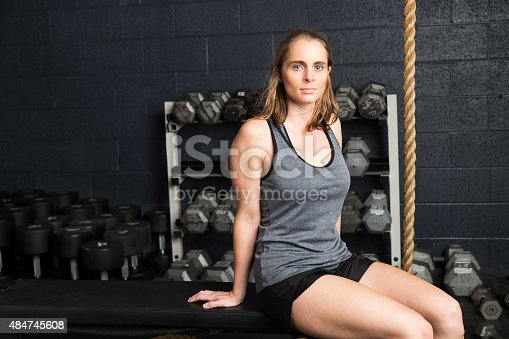 A confident woman in a gym looks at the camera.  She is wearing workout clothes and has a serious expression.  She embodies fitness and confidence.  She is sitting on a bench and you can see weights and workout equipment behind her.