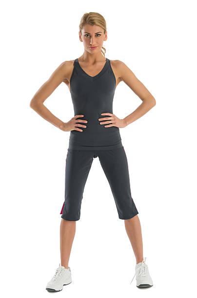 seguros de mujer en ropa deportiva con manos sobre la cadera - piernas abiertas mujer fotografías e imágenes de stock
