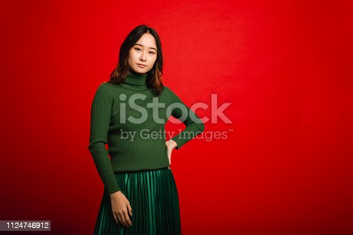 Young female adult standing infront of a red studio background. She is looking at the camera while posing.