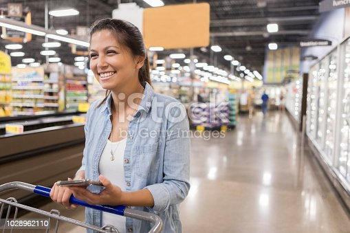 istock Confident woman shopping for groceries 1028962110