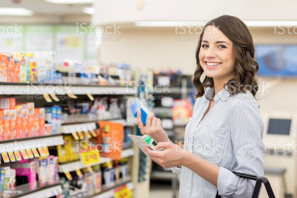 Confident woman shops for allergy medicine in a pharmacy stock photo