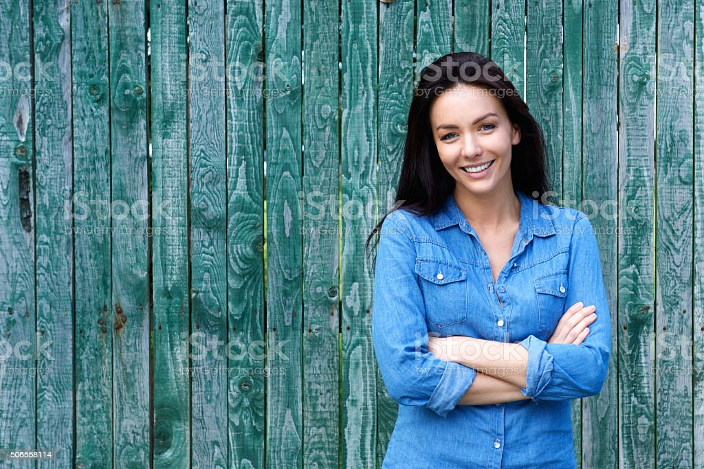 Confident woman smiling with arms crossed stock photo