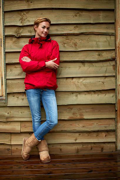 confident woman standing against wooden wall - lammfellstiefel stock-fotos und bilder