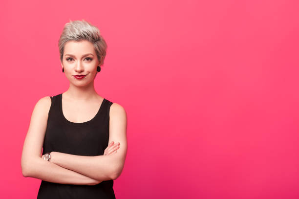 confident woman standing with arms crossed isolated over pink background stock photo