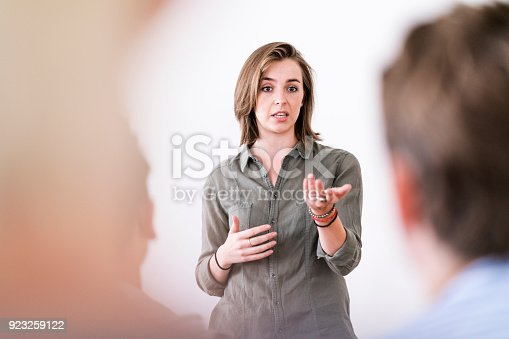 istock Confident woman talking in group therapy session 923259122