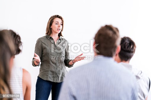 istock Confident woman talking in group therapy session 923259128
