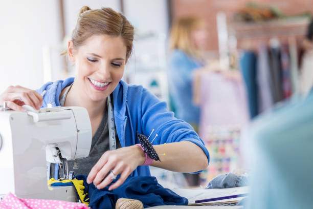Confident woman uses a sewing machine Happy Caucasian seamstress uses a sewing machine in her workshop. She is smiling confidently. She has a pin cushion around her wrist. stitching stock pictures, royalty-free photos & images