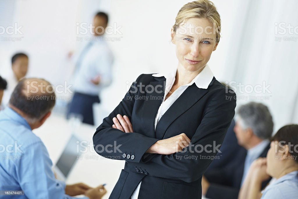 Confident woman with business people at the back royalty-free stock photo