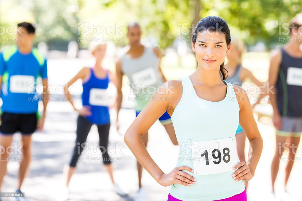 Confident Woman With Competitors In Background Before Marathon stock photo