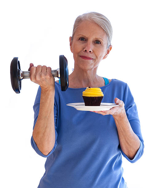 confident woman with dumbbell and cupcake - carolinemaryan stock pictures, royalty-free photos & images