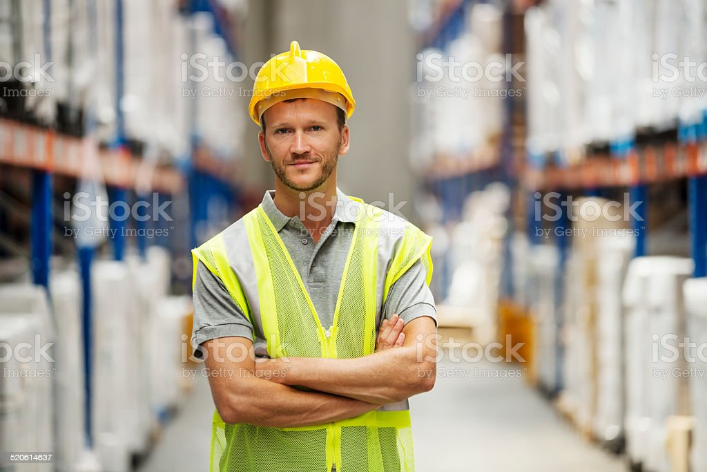 Confident worker standing in warehouse stock photo