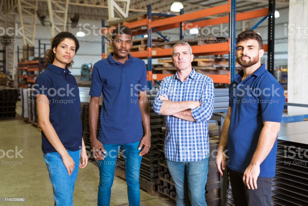 Confident workers standing in factory Portrait of instructor and apprentices in industry. Confident engineer is standing with trainees. They are in factory. 20-24 Years Stock Photo