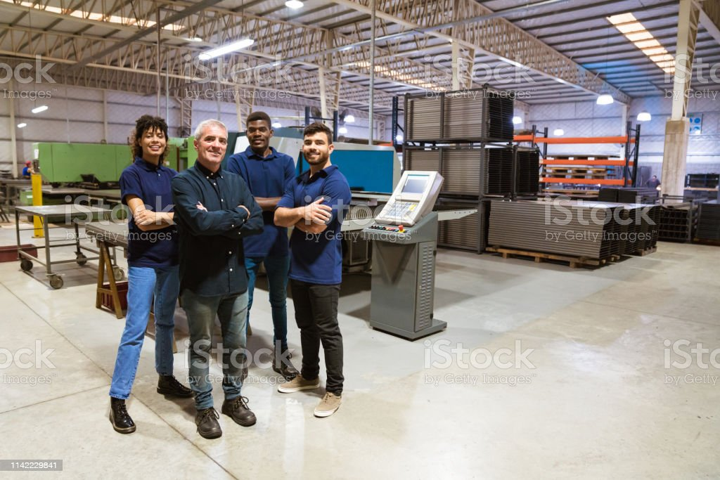 Confident workers standing in factory Portrait of multi-ethnic workers standing with arms crossed. Confident male instructor is with apprentices. They are in industry. 20-24 Years Stock Photo