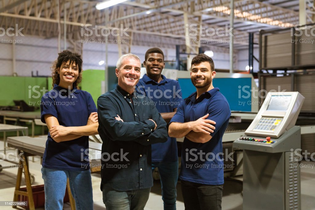 Confident workers standing in industry Portrait of smiling multi-ethnic workers in industry. Confident male instructor is with trainees. They are standing in factory. 20-24 Years Stock Photo