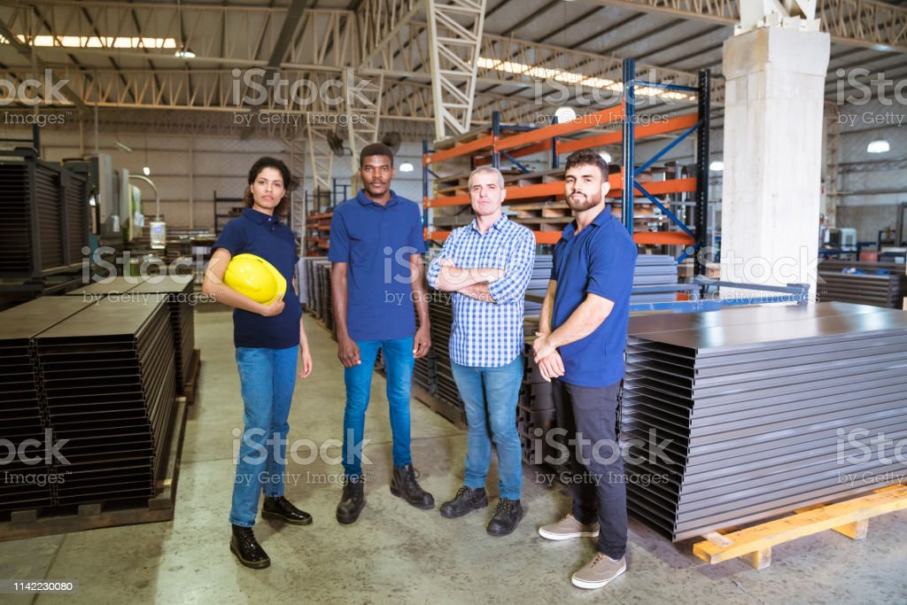 Confident workers standing in industry Portrait of engineer and apprentices in industry. Confident instructor is standing with trainees. They are at factory. 20-24 Years Stock Photo