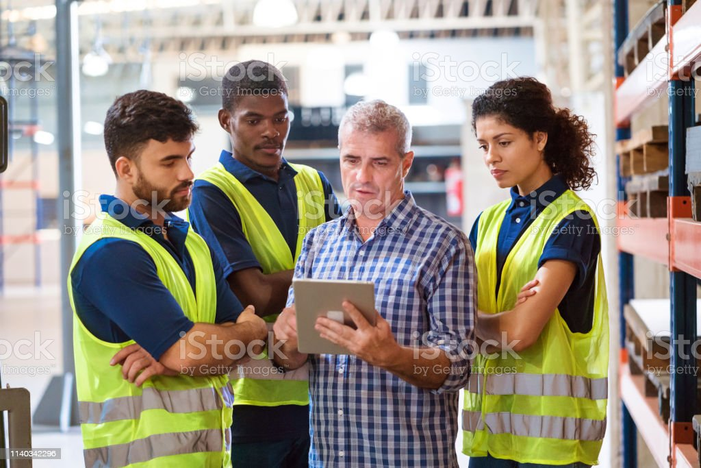 Confident workers using digital tablet in industry Confident workers with arms crossed standing in industry. Foreman is showing digital tablet to colleagues. They are working in manufacturing company. 20-24 Years Stock Photo