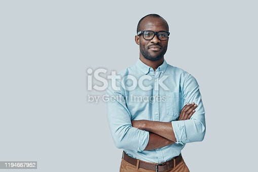 Confident young African man looking at camera and smiling while standing against grey background